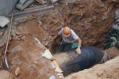 Shenzhen, China: Trabajadores que instalan los tubos de agua Foto de archivo libre de regalías
