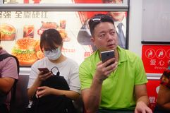 Shenzhen, China: the traffic scene of metro line 1. Some men and women are looking at their mobile phones, some are talking and so. Shenzhen metro line 1 traffic royalty free stock images