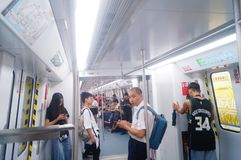 Shenzhen, China: the traffic scene of metro line 1. Some men and women are looking at their mobile phones, some are talking and so. Shenzhen metro line 1 traffic royalty free stock image
