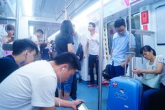 Shenzhen, China: the traffic scene of metro line 1. Some men and women are looking at their mobile phones, some are talking and so. Shenzhen metro line 1 traffic stock images