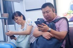 Shenzhen, China: the traffic scene of metro line 1. Some men and women are looking at their mobile phones, some are talking and so. Shenzhen metro line 1 traffic stock image