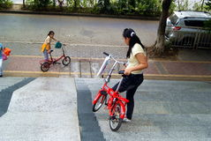 Shenzhen, China: twee meisjes die fiets dragen om bergaf te gaan Stock Afbeeldingen