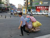 Shenzhen, China: a woman drags her collection of waste into the street Stock Photo