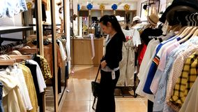 Shenzhen, China: women buy clothing and bras at a clothing store. Young women shop in clothing stores for clothes, bras, etc stock footage