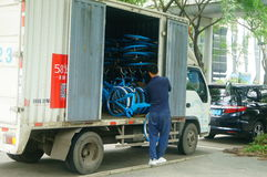Shenzhen, China: workers carry a shared bicycle from a truck. Workers carry shared bikes from trucks to the streets. In Shenzhen, china stock photo