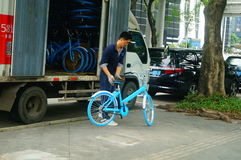 Shenzhen, China: workers carry a shared bicycle from a truck. Workers carry shared bikes from trucks to the streets. In Shenzhen, china stock image