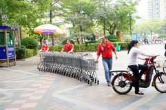 Shenzhen, China: workers in push the shopping cart Royalty Free Stock Photos