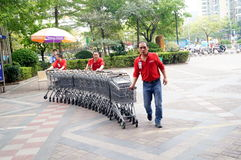 Shenzhen, China: workers in push the shopping cart Stock Photo