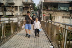 Shenzhen, China: young boys hand hold old women walk Royalty Free Stock Image