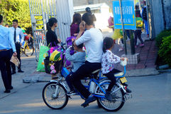 Shenzhen, China: a young father riding a bicycle carrying a little girl home from kindergarten Stock Images