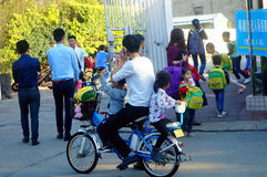 Shenzhen, China: a young father riding a bicycle carrying a little girl home from kindergarten Royalty Free Stock Photography