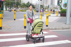 Shenzhen, China: young woman pushing a stroller Royalty Free Stock Photo