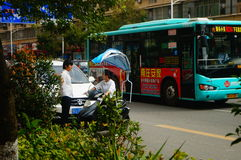 Shenzhen, China: a young woman riding an electric car chats with a man on the road Stock Photo