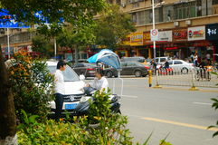 Shenzhen, China: a young woman riding an electric car chats with a man on the road Stock Image