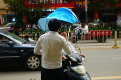 Shenzhen, China: a young woman riding an electric car chats with a man on the road Stock Photography