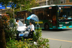 Shenzhen, China: a young woman riding an electric car chats with a man on the road Royalty Free Stock Photo