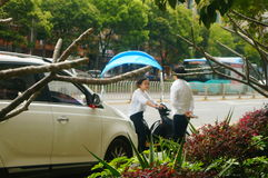 Shenzhen, China: a young woman riding an electric car chats with a man on the road Royalty Free Stock Photos