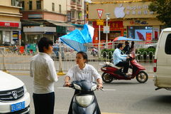 Shenzhen, China: a young woman riding an electric car chats with a man on the road Royalty Free Stock Images
