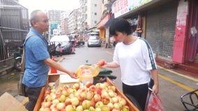 Shenzhen, Chine : les jeunes femmes achètent des pêches image libre de droits