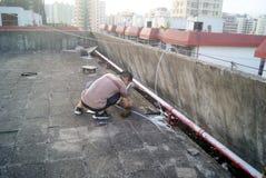 Shenzhen, Chiny: instalacja satelitarnego TV odbiorca Fotografia Stock
