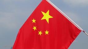 Shenzhen, Chiny: jaskrawa pięciogwiazdkowa czerwona flaga wiesza na drodze witać przyjazd święto państwowe zbiory
