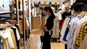 Shenzhen, Chiny: kobiety kupuj? odzie? i staniki przy sklepem odzie?owym zbiory