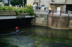 Shenzhen, Chiny: sanacja pracownicy czyścą up banialuki w rzece zdjęcia royalty free