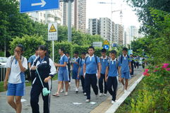 Shenzhen, Cina: gli studenti della scuola secondaria vanno a casa sulla via di casa Fotografie Stock