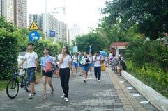 Shenzhen, Cina: gli studenti della scuola secondaria vanno a casa sulla via di casa Fotografia Stock