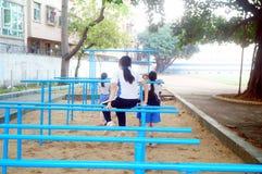Shenzhen, Cina: gli studenti femminili della scuola secondaria nella barra orizzontale si esercitano Fotografia Stock Libera da Diritti
