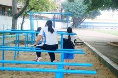 Shenzhen, Cina: gli studenti femminili della scuola secondaria nella barra orizzontale si esercitano Immagine Stock Libera da Diritti
