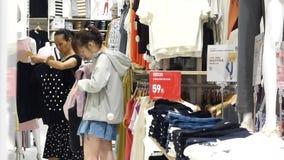 Shenzhen, Cina: i clienti comperano per i vestiti al negozio di vestiti dei uniqlo alla notte archivi video