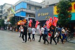 Shenzhen, Cina: i giovani per alzare l'insegna della pubblicità di Internet, pubblicità liberano Internet Fotografie Stock