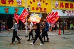 Shenzhen, Cina: i giovani per alzare l'insegna della pubblicità di Internet, pubblicità liberano Internet Fotografia Stock Libera da Diritti