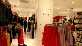 Shenzhen, Cina: Il paesaggio interno del negozio dell'indumento di Uniqlo, donne sta scegliendo i vestiti archivi video