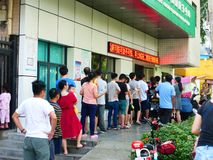 SHENZHEN, CINA: Mamma, papà, ecc prenda i loro bambini per vaccinare nel centro di servizio sanitario della comunità fotografia stock