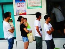 SHENZHEN, CINA: Mamma, papà, ecc prenda i loro bambini per vaccinare nel centro di servizio sanitario della comunità fotografia stock libera da diritti
