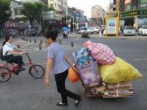 Shenzhen, Cina: una donna trascina la sua raccolta di spreco nella via Fotografia Stock Libera da Diritti