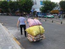 Shenzhen, Cina: una donna trascina la sua raccolta di spreco nella via Fotografia Stock