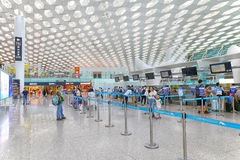 Shenzhen international airport check in counters. Passengers at the check in counters of the departure hall of shenzhen international airport, china royalty free stock photos