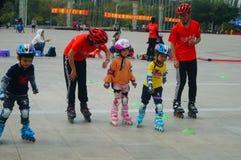 Shenzhen Kina: Barn öva att åka skridskor för rulle på sportarna kvadrerar arkivbild