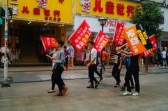 Shenzhen Kina: ungdomarsom lyfter banret av internetadvertizingen, publicitet frigör internet Royaltyfri Foto