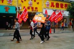 Shenzhen Kina: ungdomarsom lyfter banret av internetadvertizingen, publicitet frigör internet Fotografering för Bildbyråer