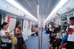 Shenzhen, China: the traffic scene of metro line 1. Some men and women are looking at their mobile phones, some are talking and so. Shenzhen metro line 1 traffic stock photo