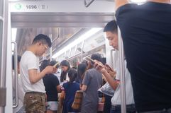 Shenzhen, China: the traffic scene of metro line 1. Some men and women are looking at their mobile phones, some are talking and so. Shenzhen metro line 1 traffic royalty free stock photography