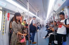 Shenzhen, China: the traffic scene of metro line 1. Some men and women are looking at their mobile phones, some are talking and so. Shenzhen metro line 1 traffic royalty free stock photo