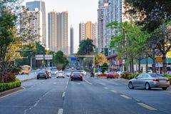 Shenzhen upptagen stadsgata med den rörande bilen, motorcykel, kontorsbyggnad, skyskrapor arkivfoton