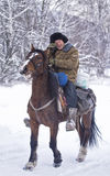 Shepherd or cowboy rides horse on the winter snowy forest on Novemer 1, 2016 Altai, Russia Royalty Free Stock Photography