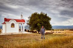 A shepherd in front of a little chapel and a herd of sheep