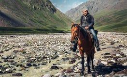 Shepherd la impulsión la manada que se sienta en un caballo en el fondo de Fotografía de archivo libre de regalías